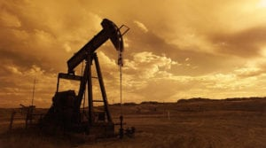 Oil pump jack in a cloudy desert sunset.
